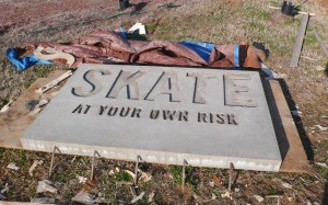 Skate At Your Own Risk embedded sign at the Green River skatepark. Image courtesy Epicenter.